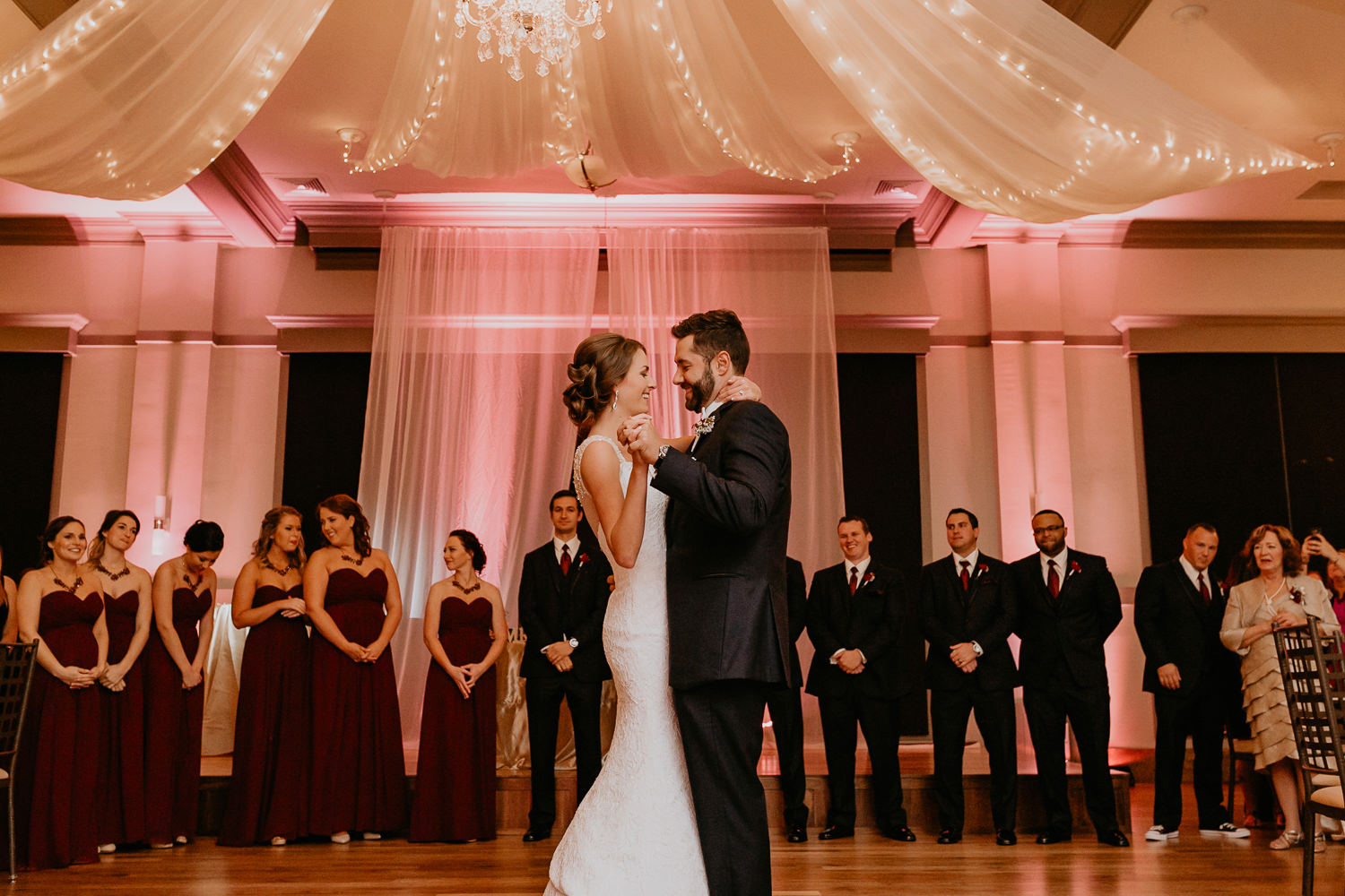 wide view of newlyweds facing each other during first dance