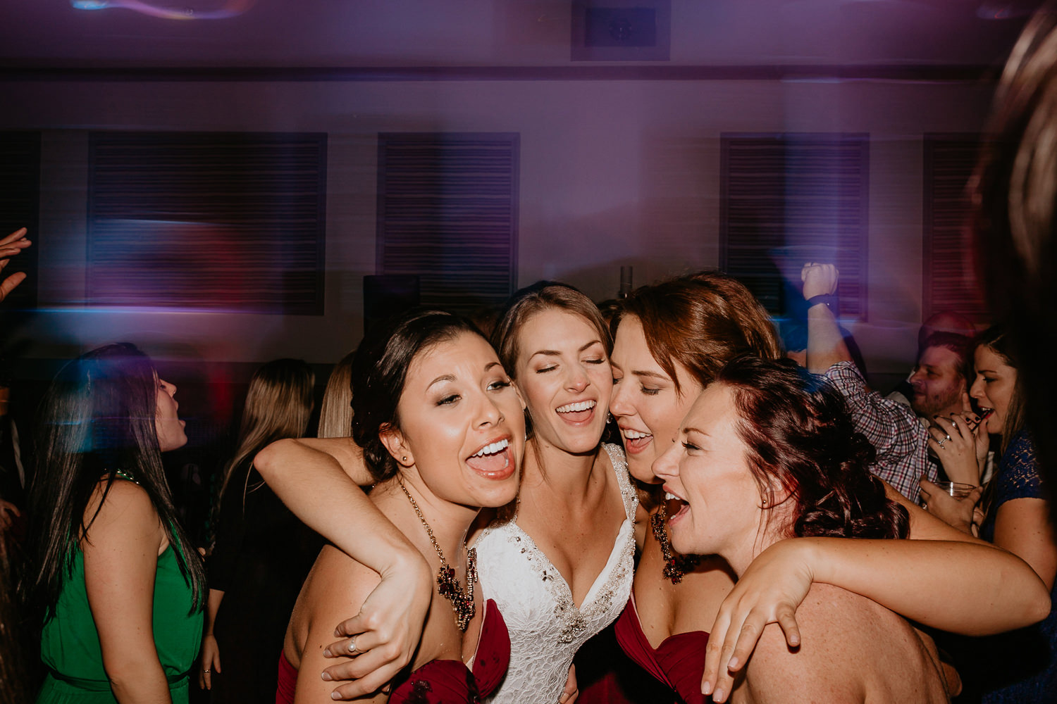 bride with her arms around her bridesmaids all head touching and singing