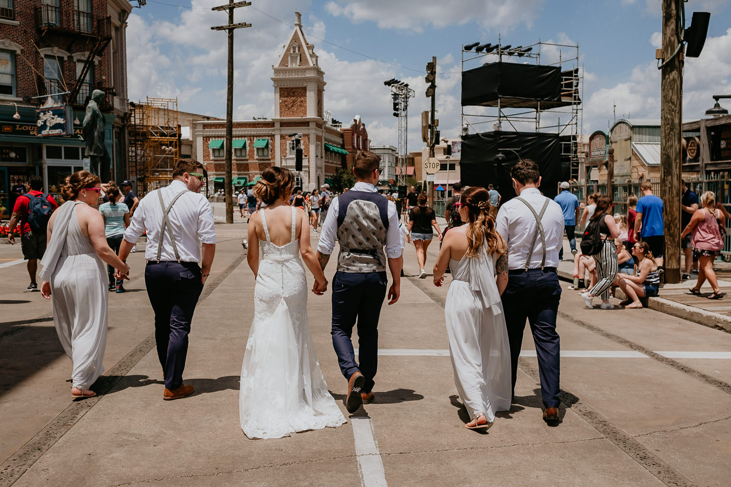 bridal party walking side by side all holding hands entering universal studios