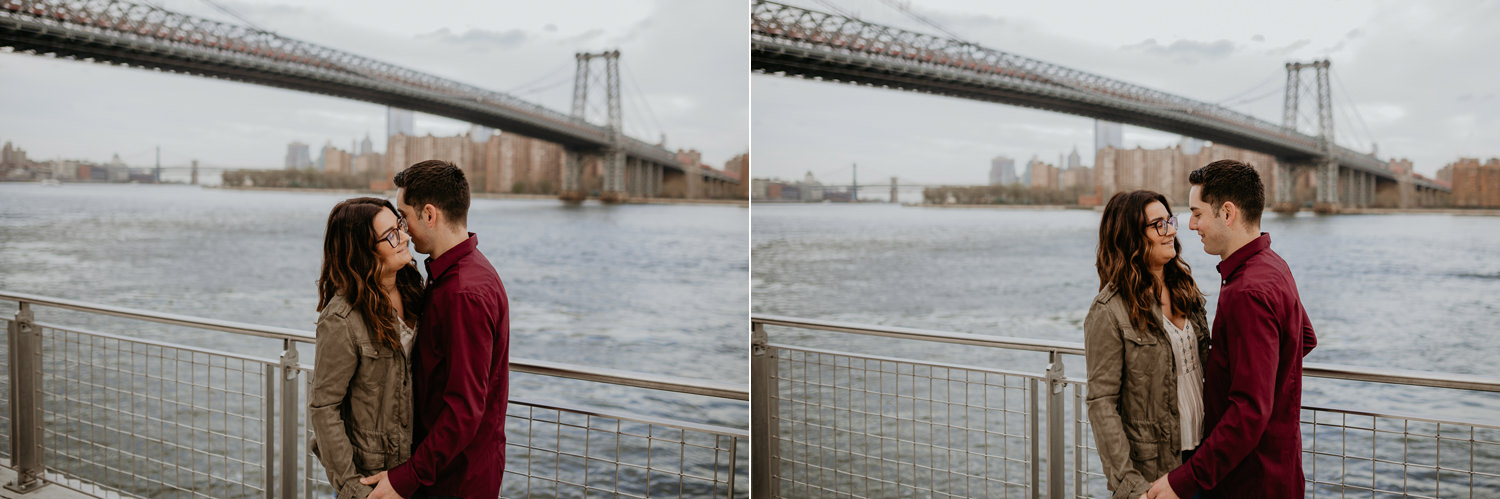 couple holding hands smiling at each other Williamsburg Bridge in background