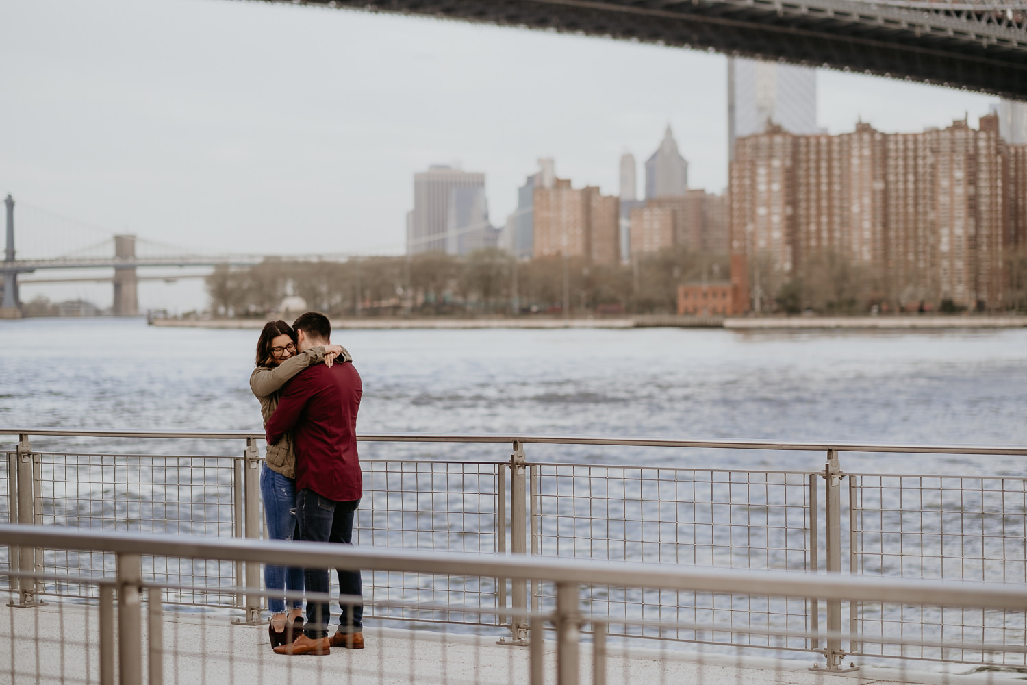 wide view of couple hugging and view of manhattan skyline and Williamsburg Bridge