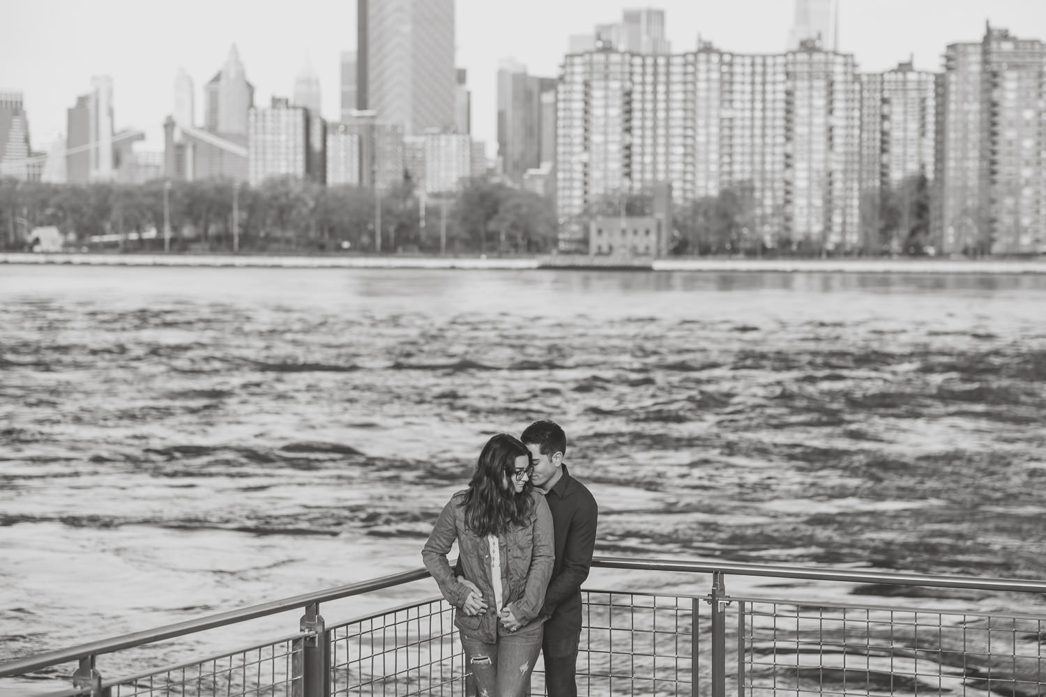 black and white wide view of couple at the edge of domino park with nyc skyline