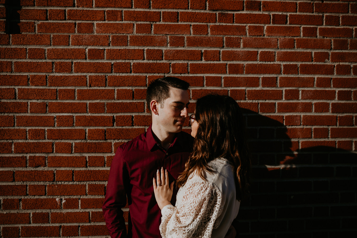 couple together looking at each other her hands on his chest in front of brick wall