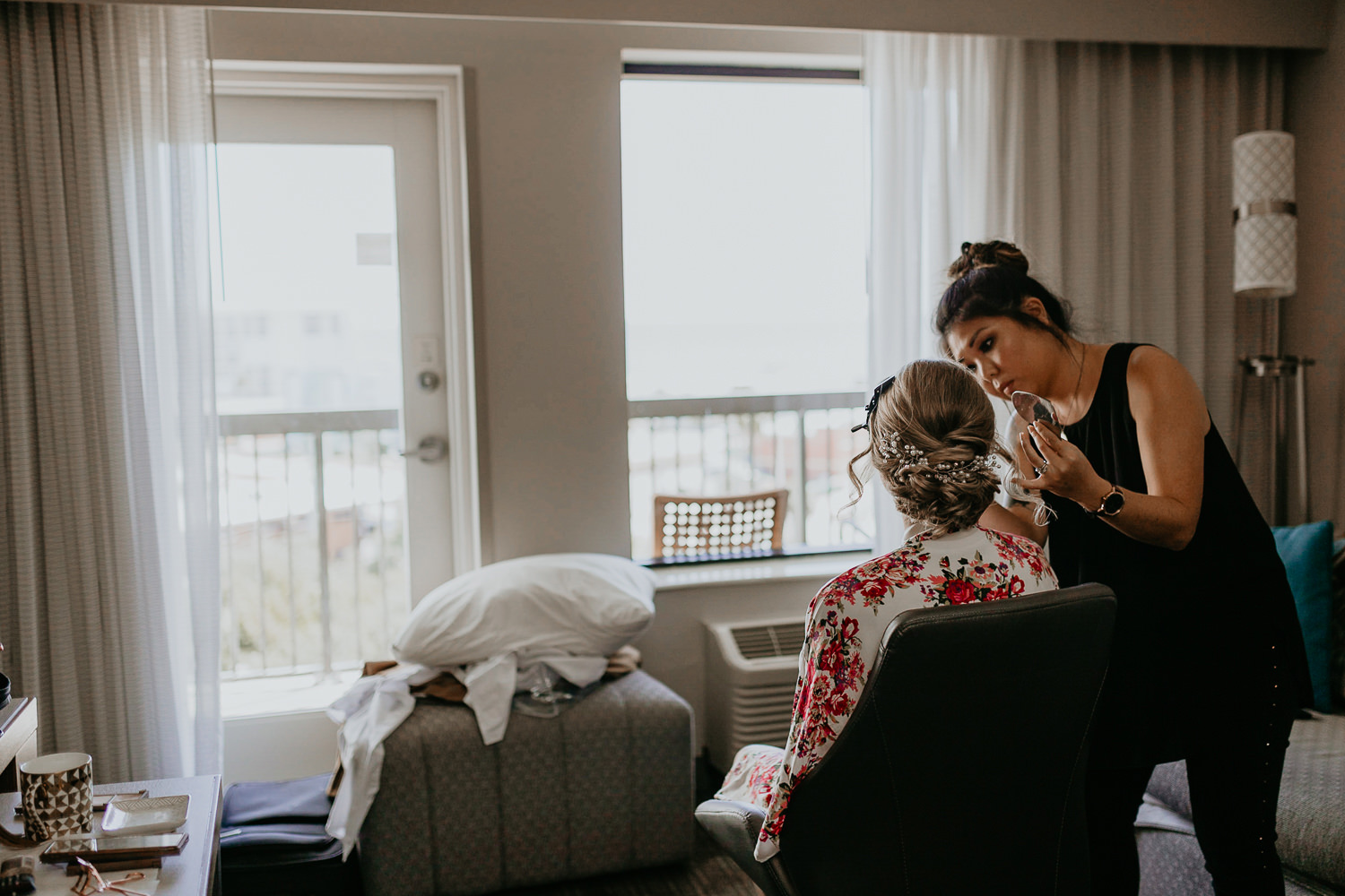 view from behind, bride in chair, makeup artist applying makeup