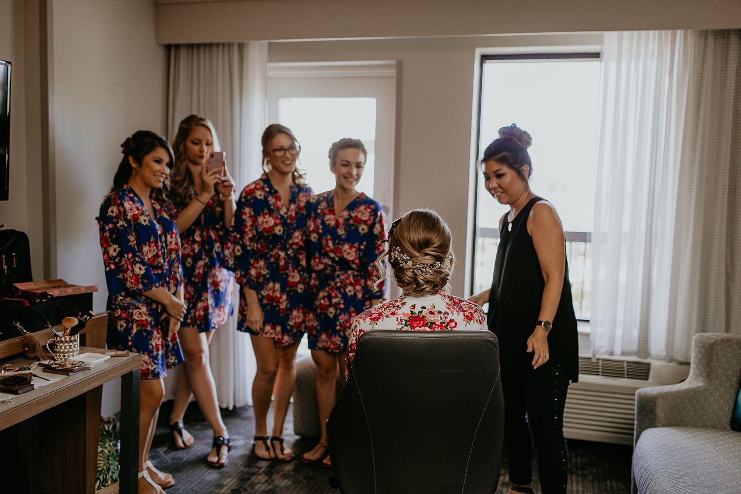 bridesmaids smiling at bride and taking pictures, all wearing robes