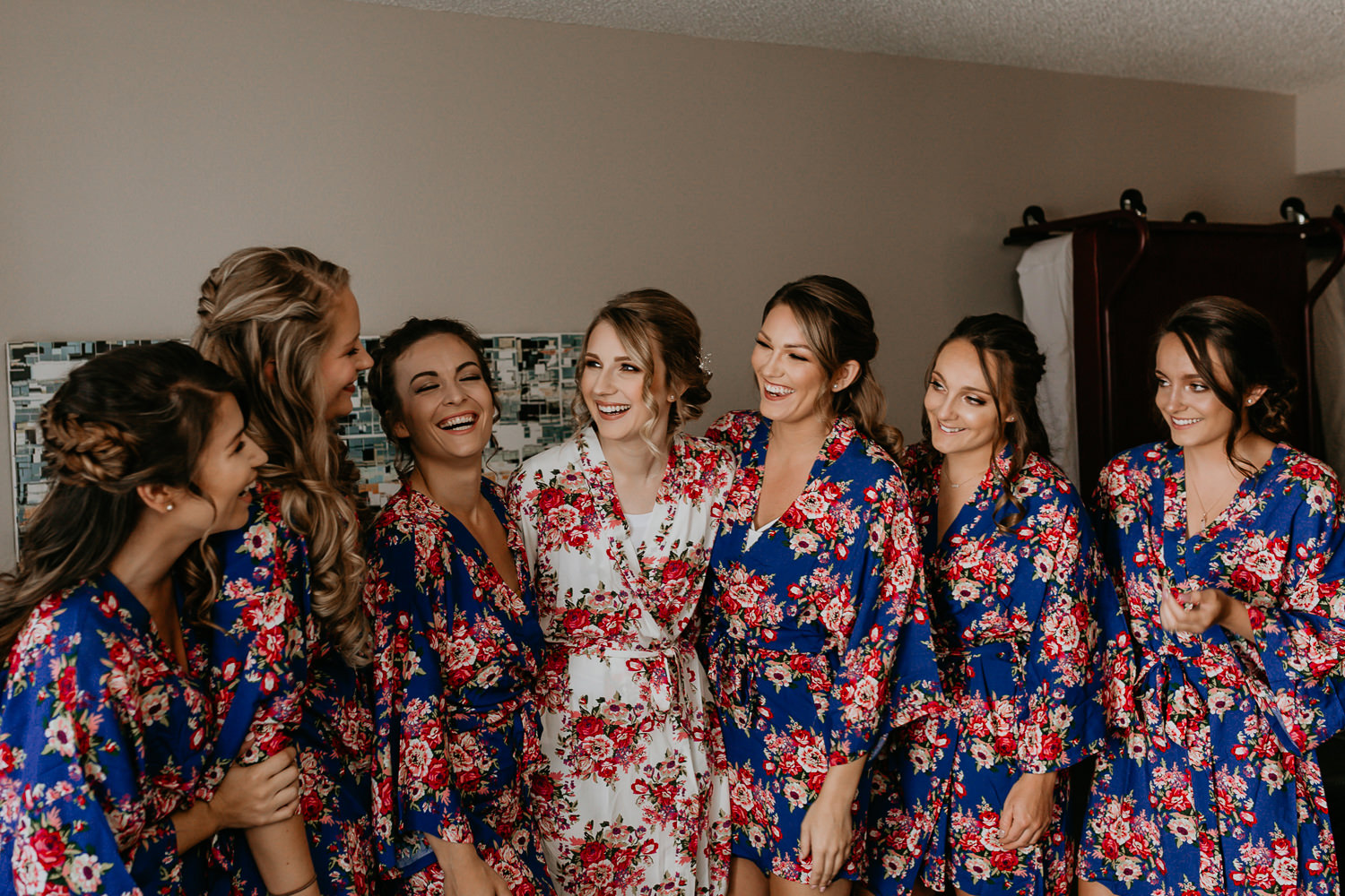 bride and bridesmaids laughing wearing flowery robes