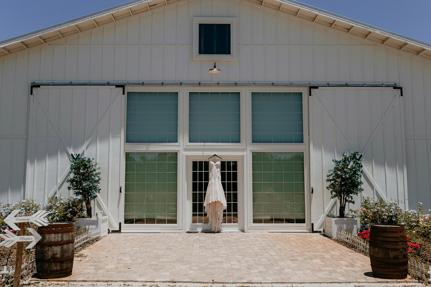 wide shot of ever after barn, wedding dress hanging on the door