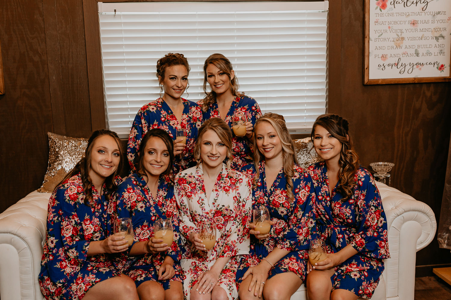 bride and bridesmaids sitting on couch holding champagne glasses in their robes