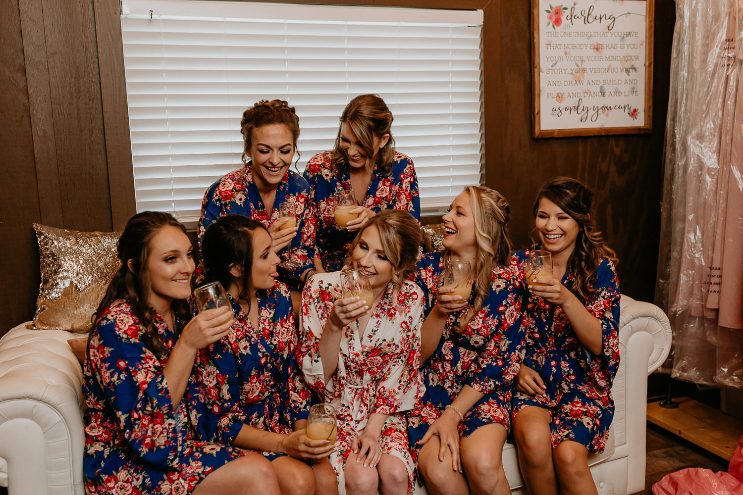 close up of bridesmaids laughing sitting on couch holding champagne glasses