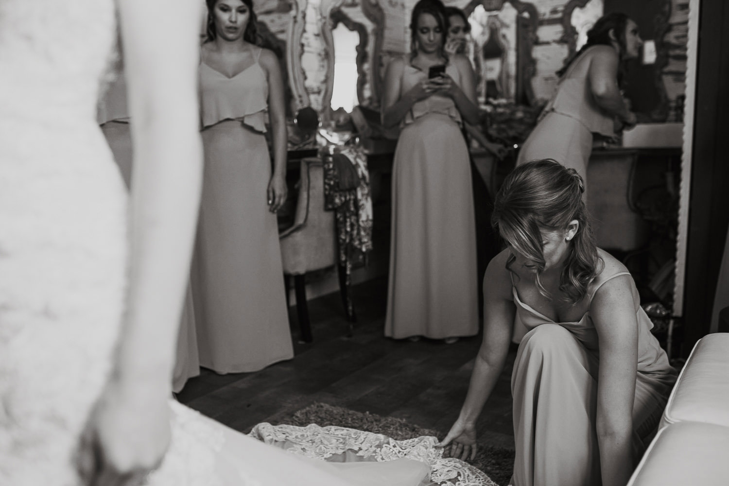 bridesmaid helping with wedding dress on bride