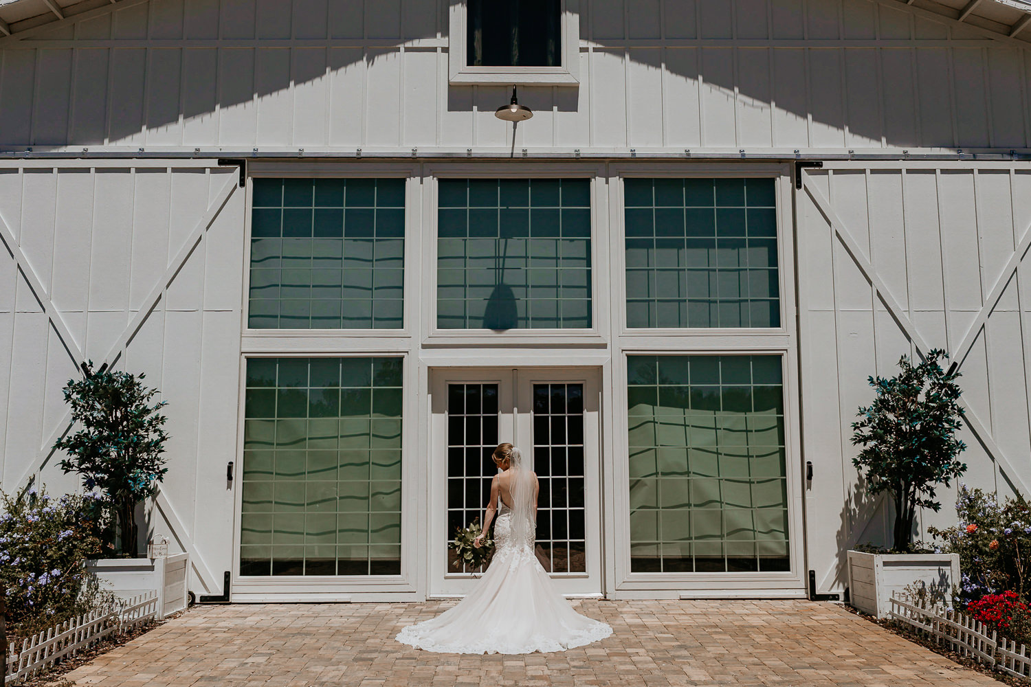 wide shot of bride, her dress wide, holding flowers in front of white barn doors