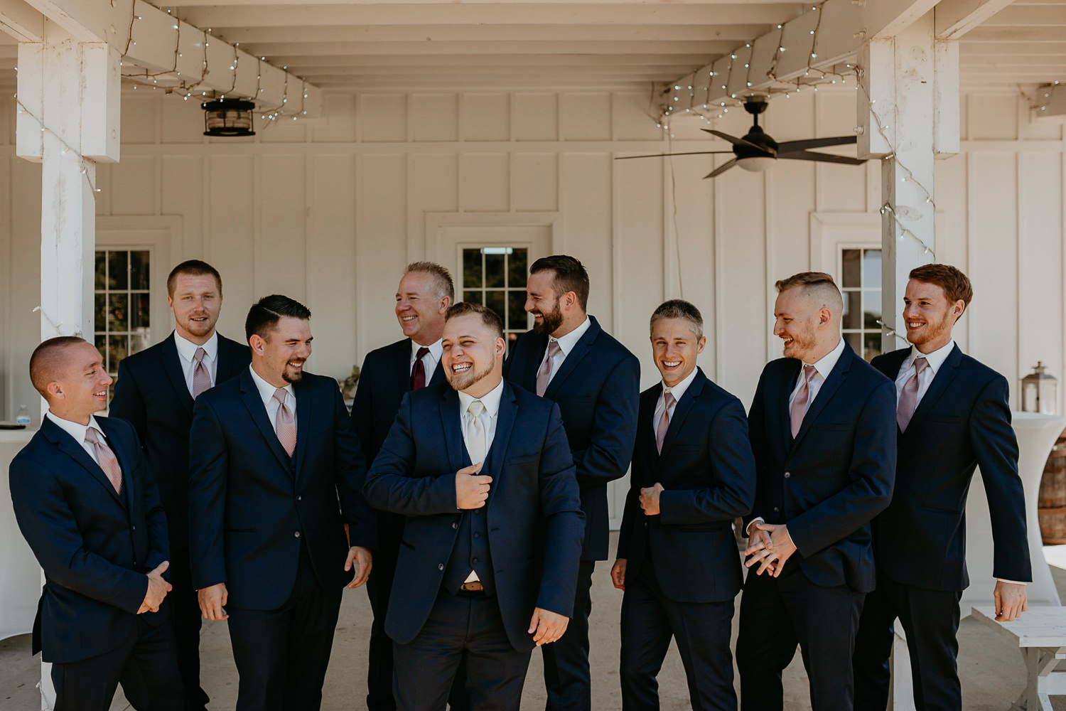 groom and his groomsmen all lined up and laughing at ever after farms