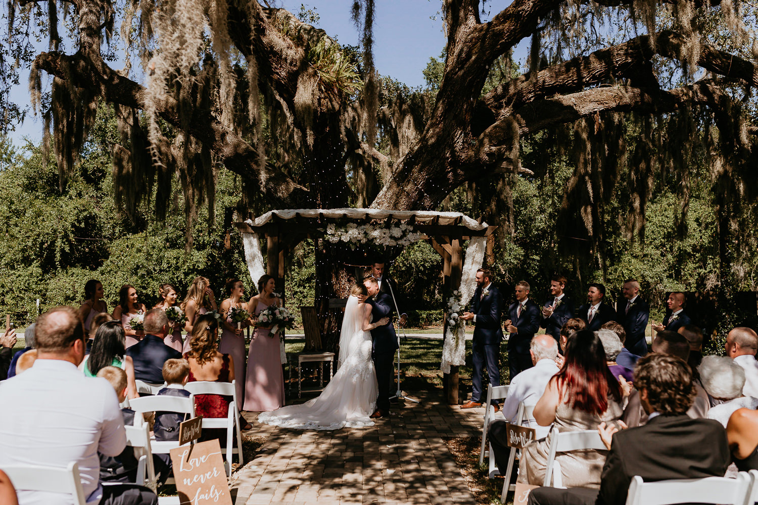newlyweds first kiss at ever after farms under huge Spanish moss covered tree