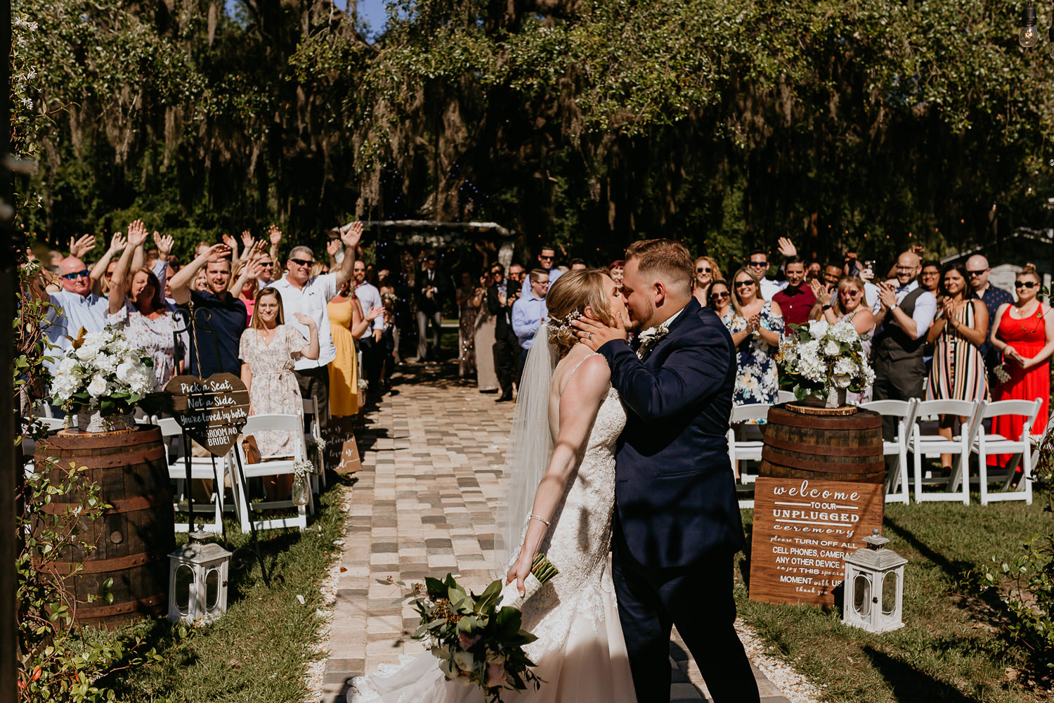 newlyweds passionately kissing, ceremony guests in background cheering