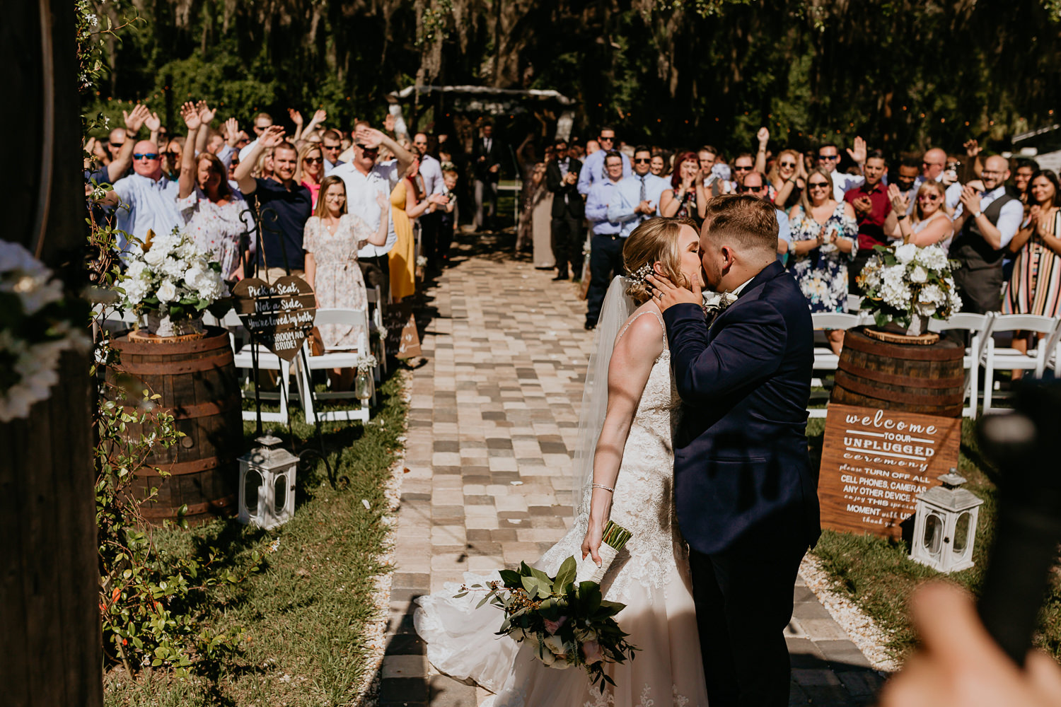 groom kissing his new bride at the end of the aisle, all ceremony wedding guests cheering