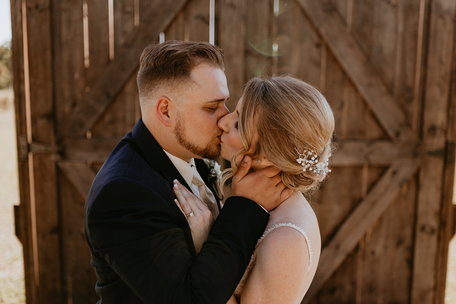 groom kissing bride in front of wooden barn doors, his hands on her face