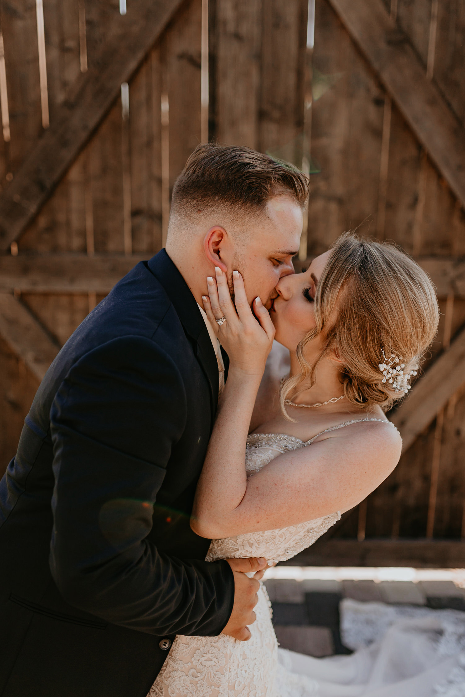 newlyweds kissing, brides hand on grooms face, in front of wooden barn doors