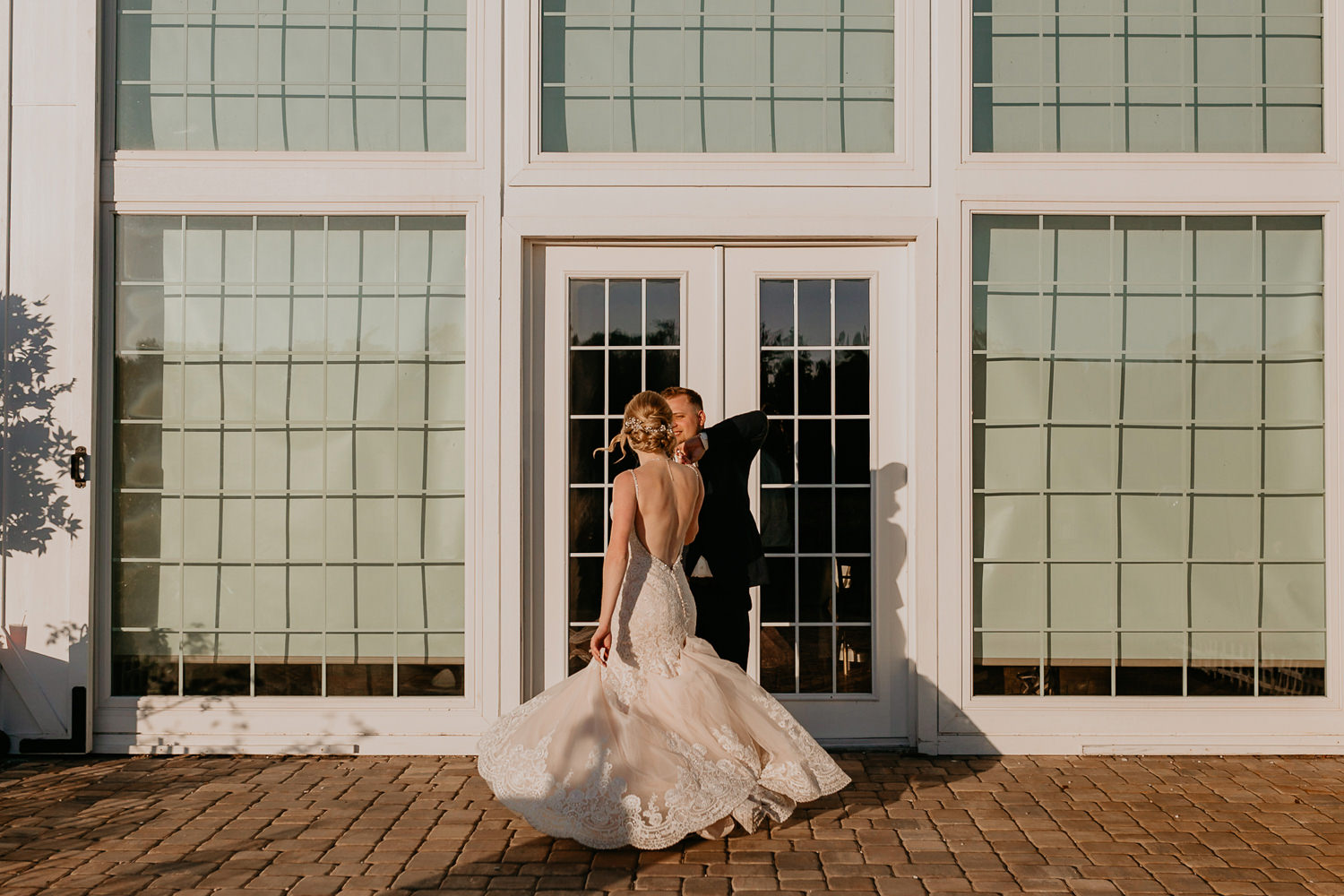 groom spinning bride, her dress dancing in the air in front of farm barn doors