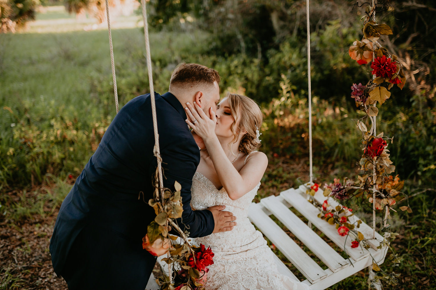 overhead shot of newlyweds kissing, bride sitting on flowery swing bench