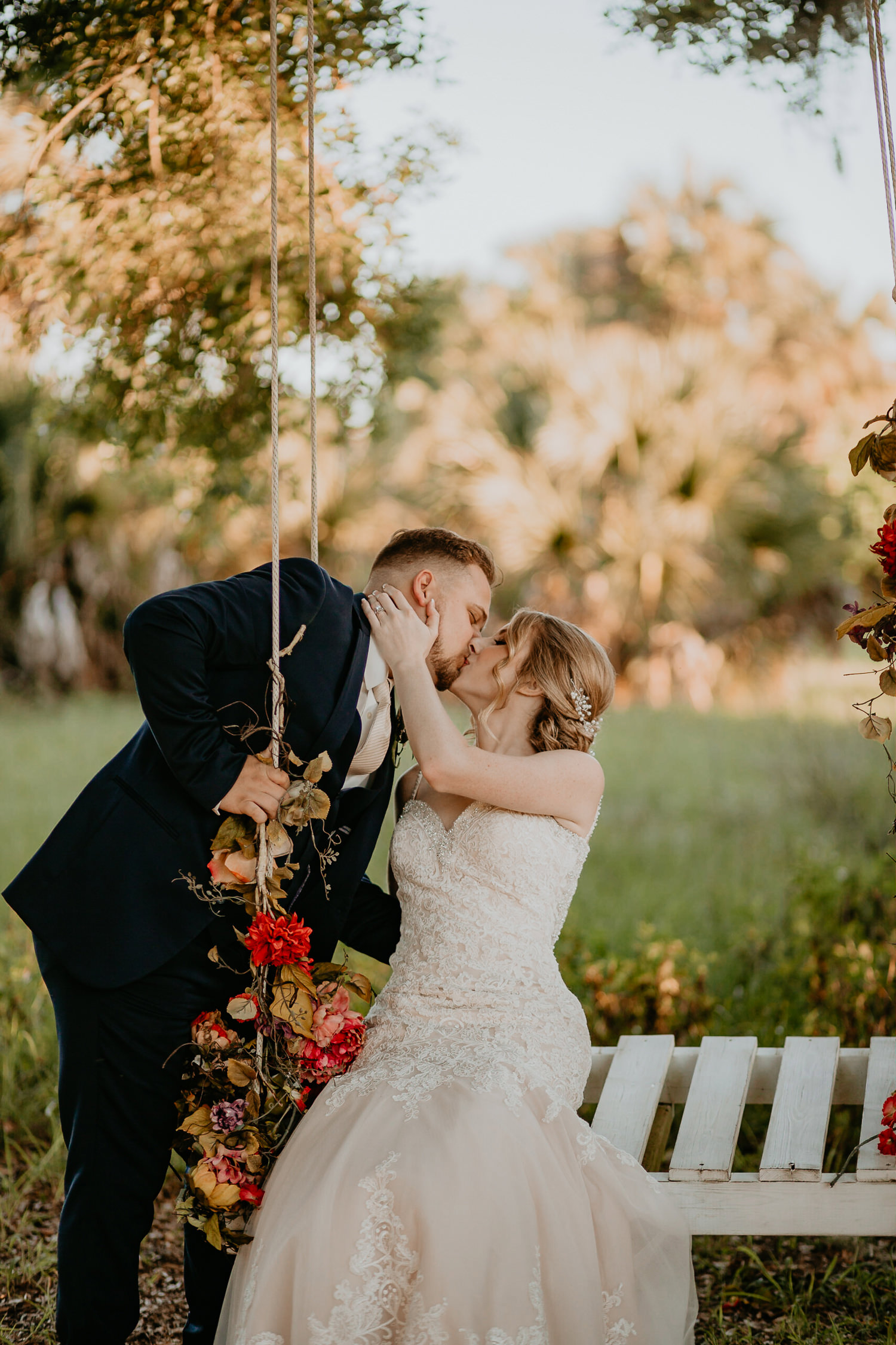 bride sitting on flowery swing bench, groom standing leaning towards her, both kissing