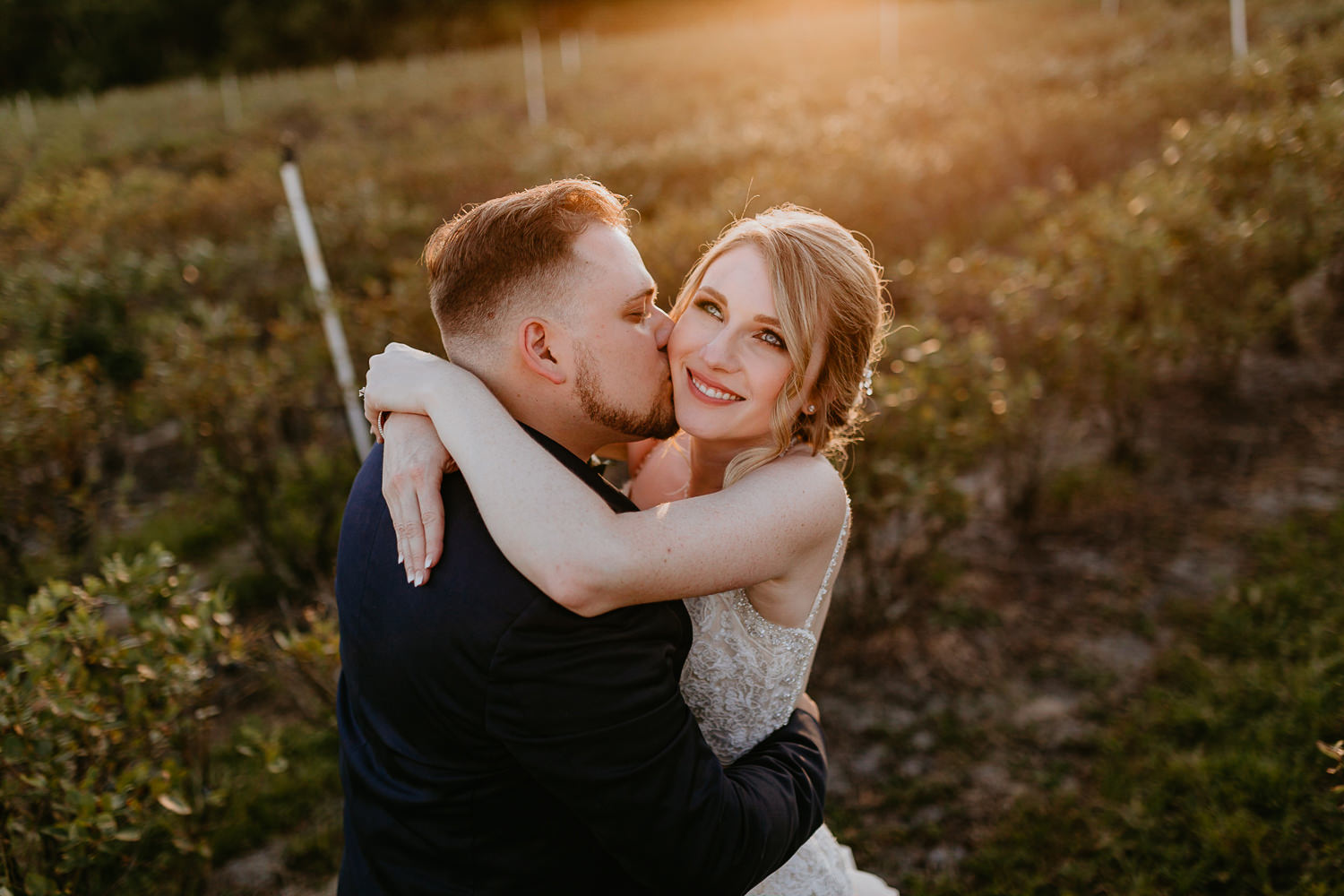 newlyweds intimately kissing with sunset flares