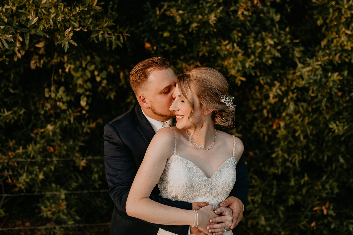 groom kissing bride on the cheek from behind with green bush as background