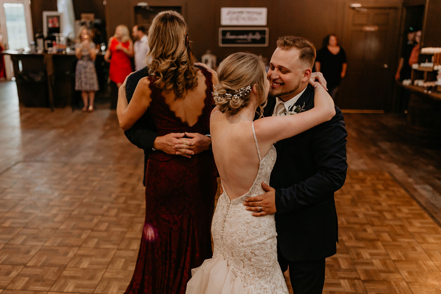 newlyweds dancing arms around each other, parents also dancing