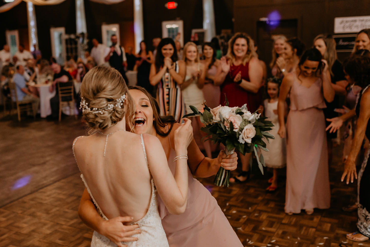 bridesmaid that caught the bouquet hugging the bride, guests applauding