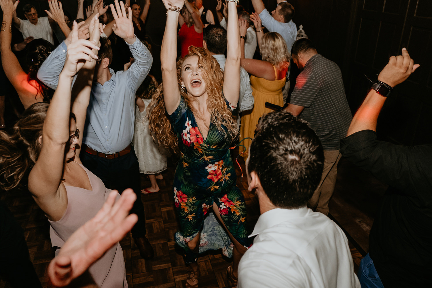 wedding guest with red curly hair singing and hands in the air