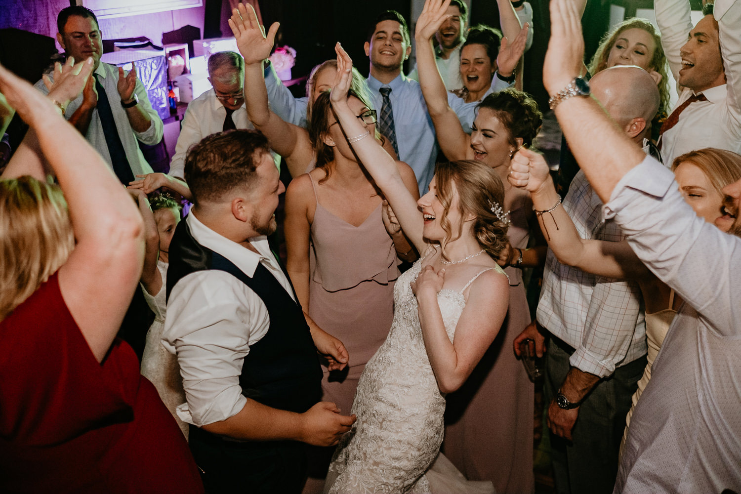 newlyweds dancing hands surrounded by all friends everyone's hands in the air