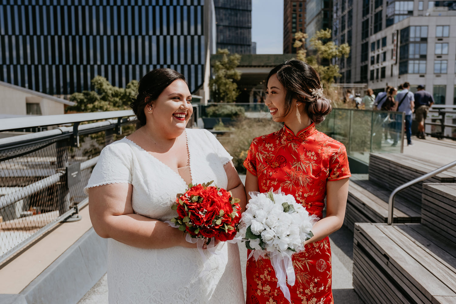 two brides wearing a white wedding dress and red Chinese dress smiling at each other