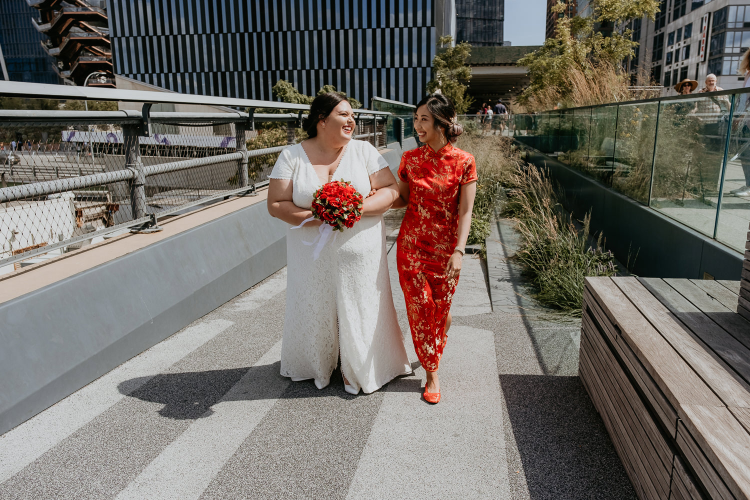 two brides walking and smiling at each other, their arms connected