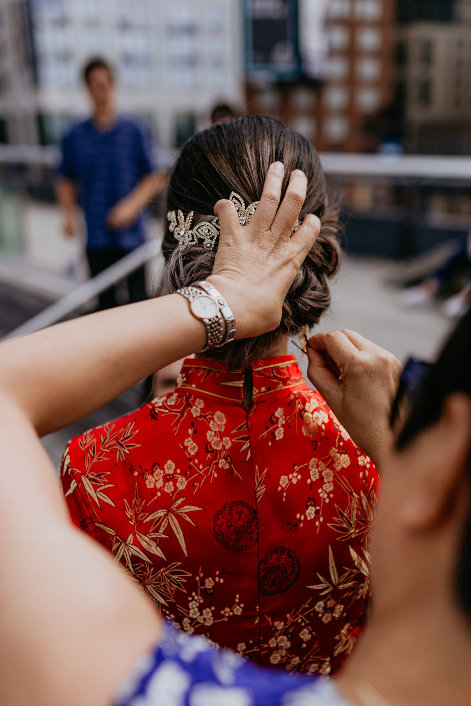 close up of mom fixing brides hair, bride wearing red Chinese wedding dress