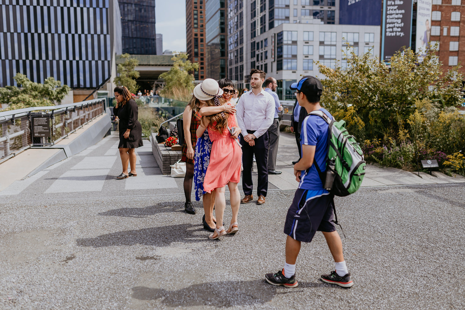 wide shot of family and friends hugging each other at ceremony site at the high line