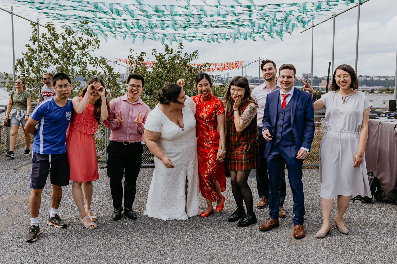 two brides surrounded by friends on each side lined up laughing at the camera