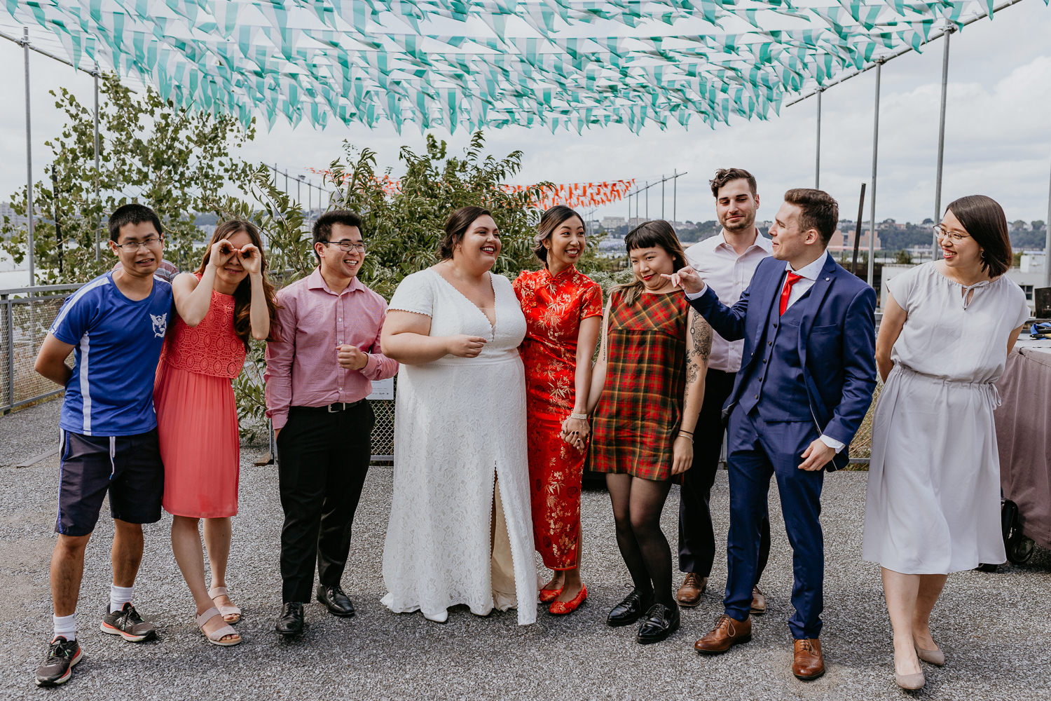 two brides surround by friends on both sides laughing at each other