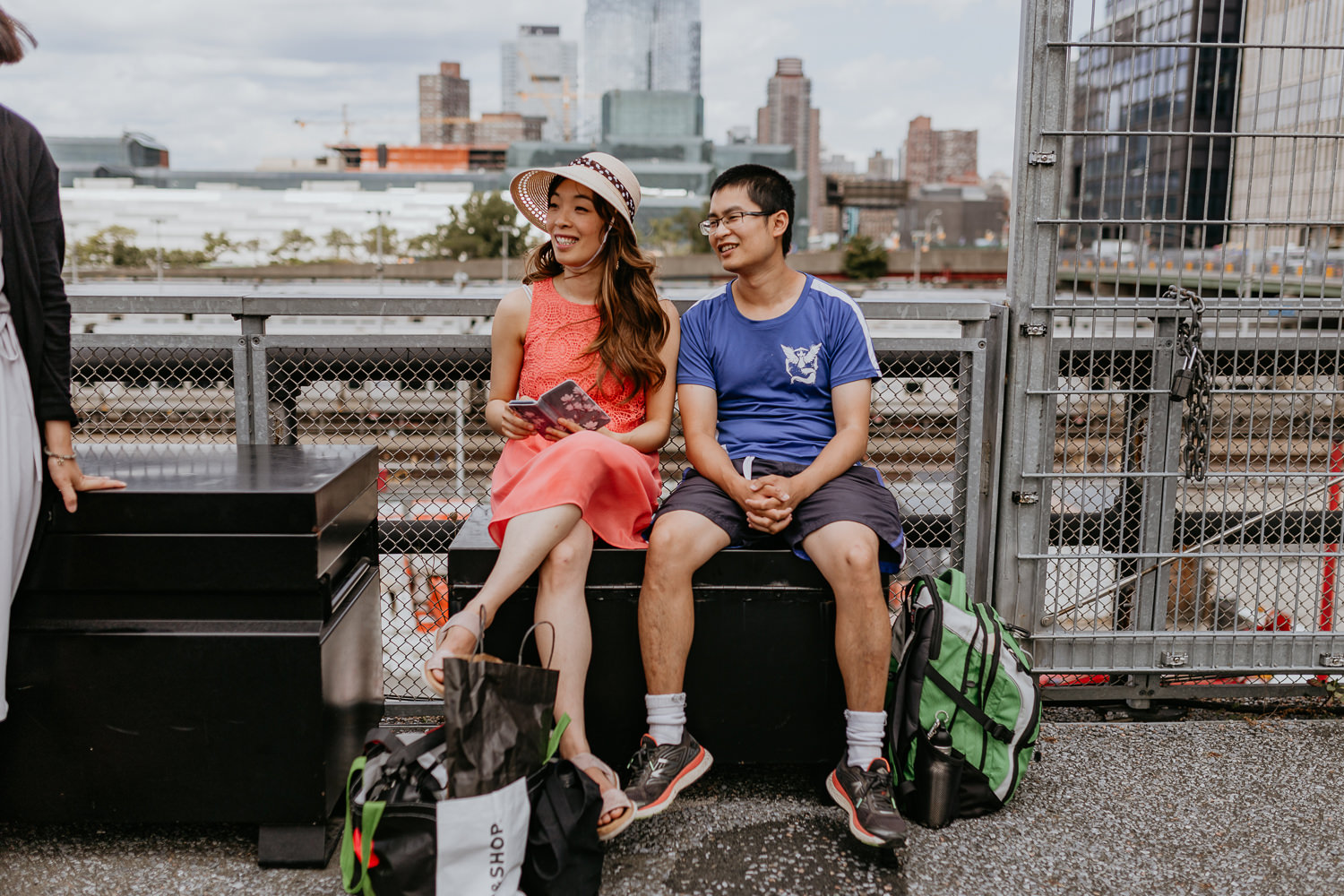 asian male and female friends of the brides sitting with the views on NYC on the background