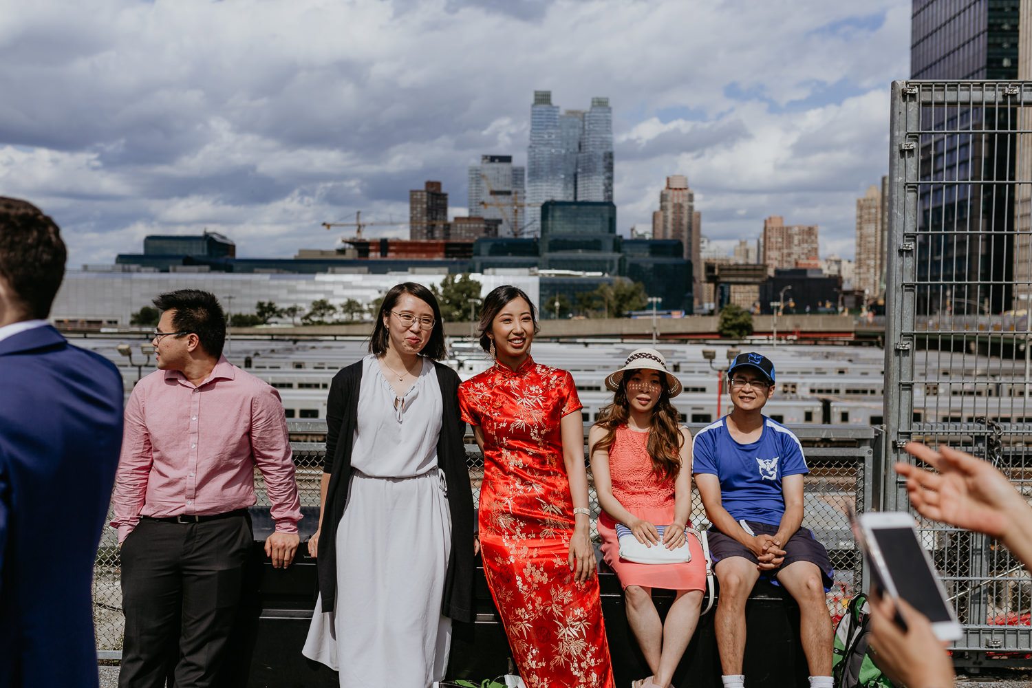 bride in red Chinese dress with her friends sitting with the NYC city views in the background