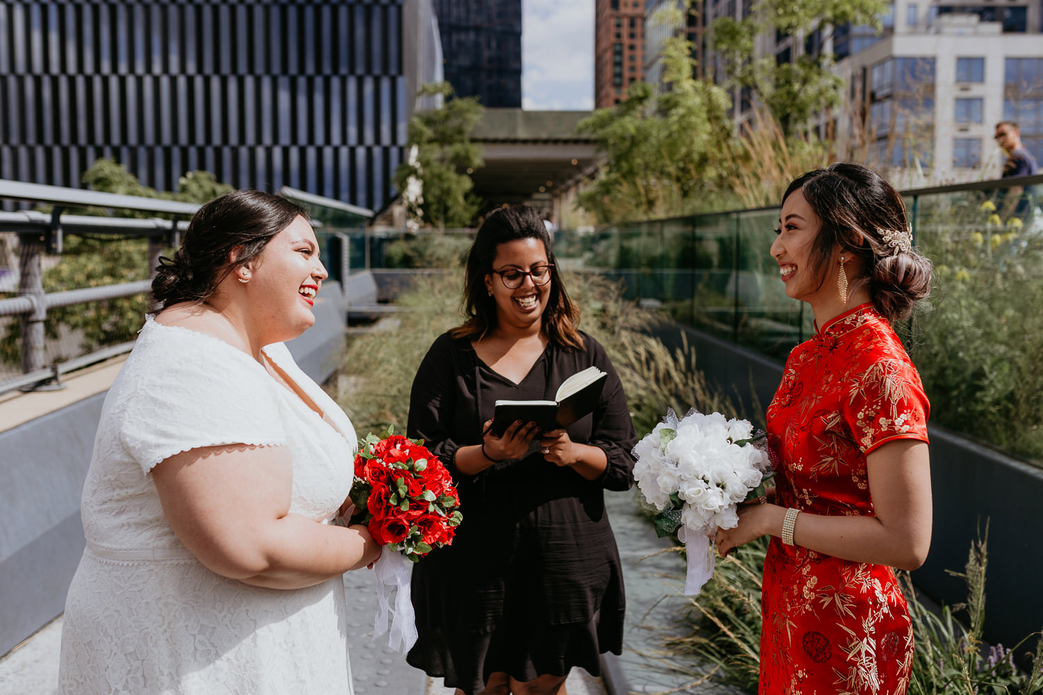 two brides facing each other officiant in the middle, everyone laughing