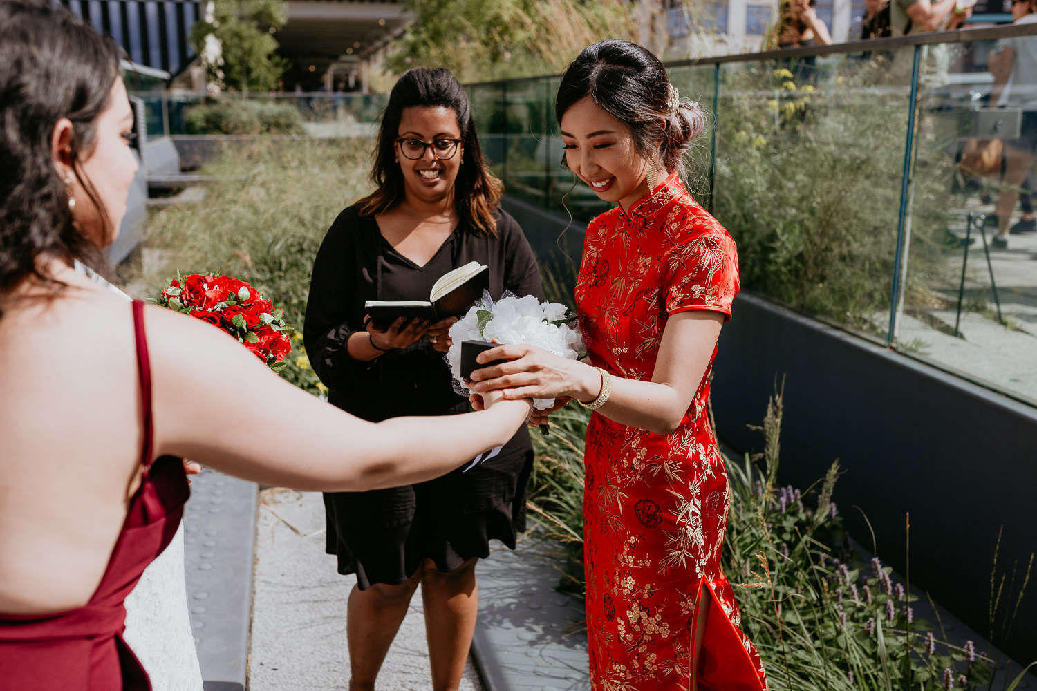 rings being handed to bride in red Chinese wedding dress