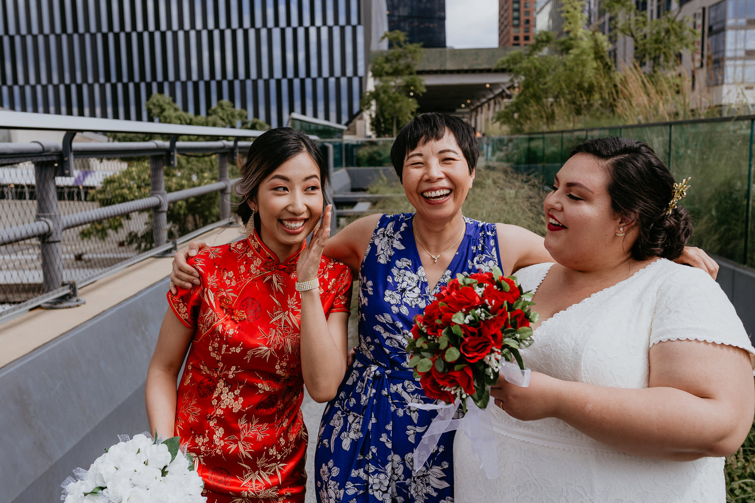 close up of two brides with mom in the middle all laughing