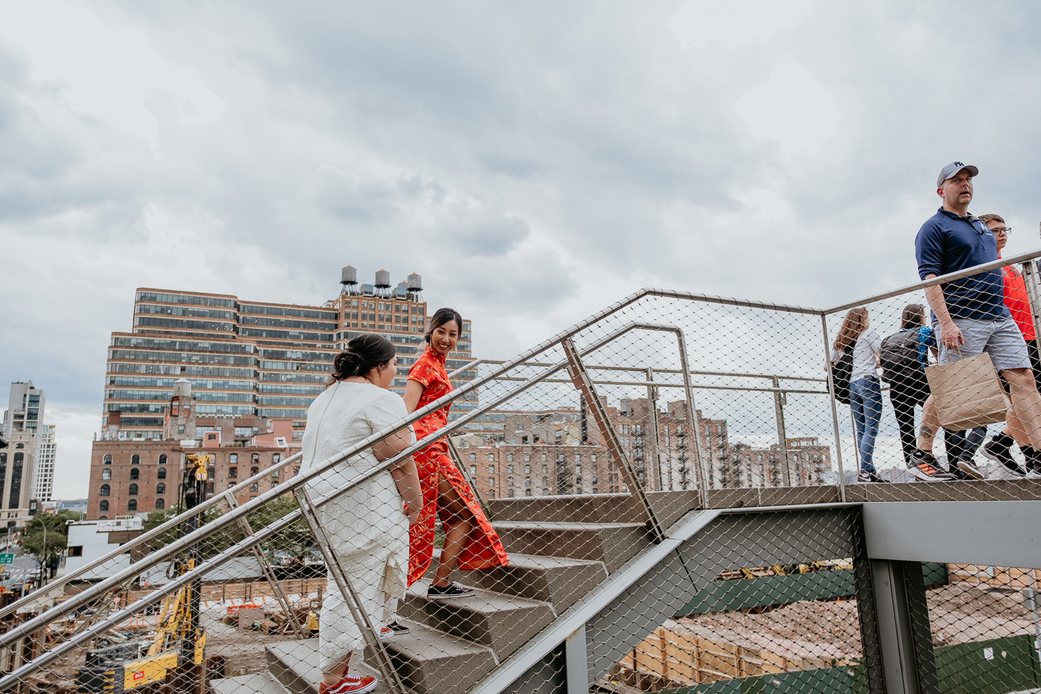 two brides walking up the stairs at the high line, one leading the other smiling