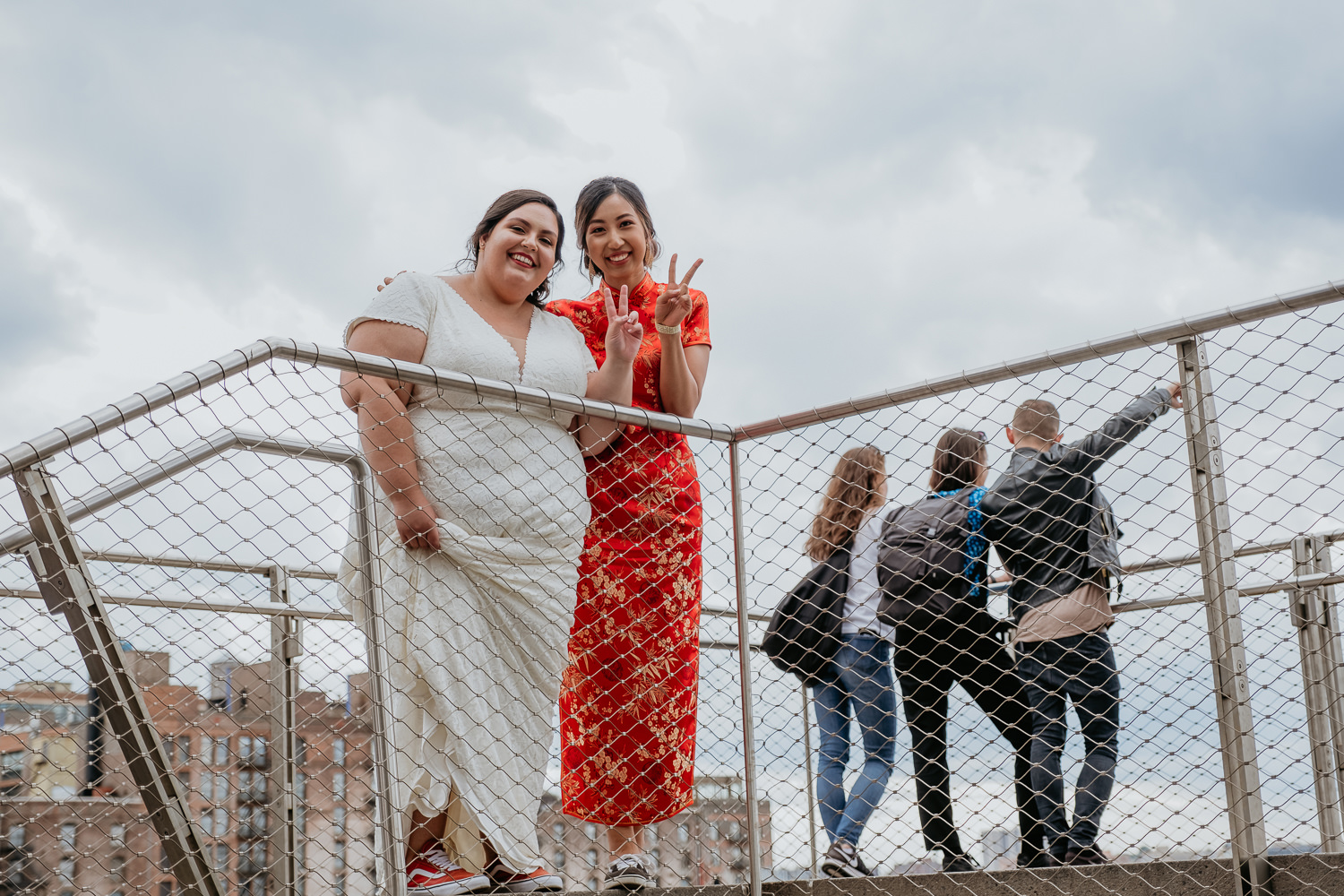 close up of two brides at the top of the stairs smiling at camera with peace signs