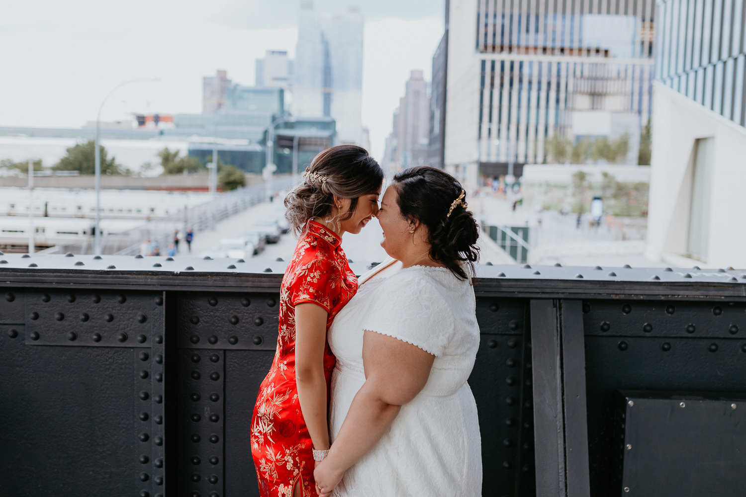 two brides facing each other holding hands and noses touching on high line bridge nyc