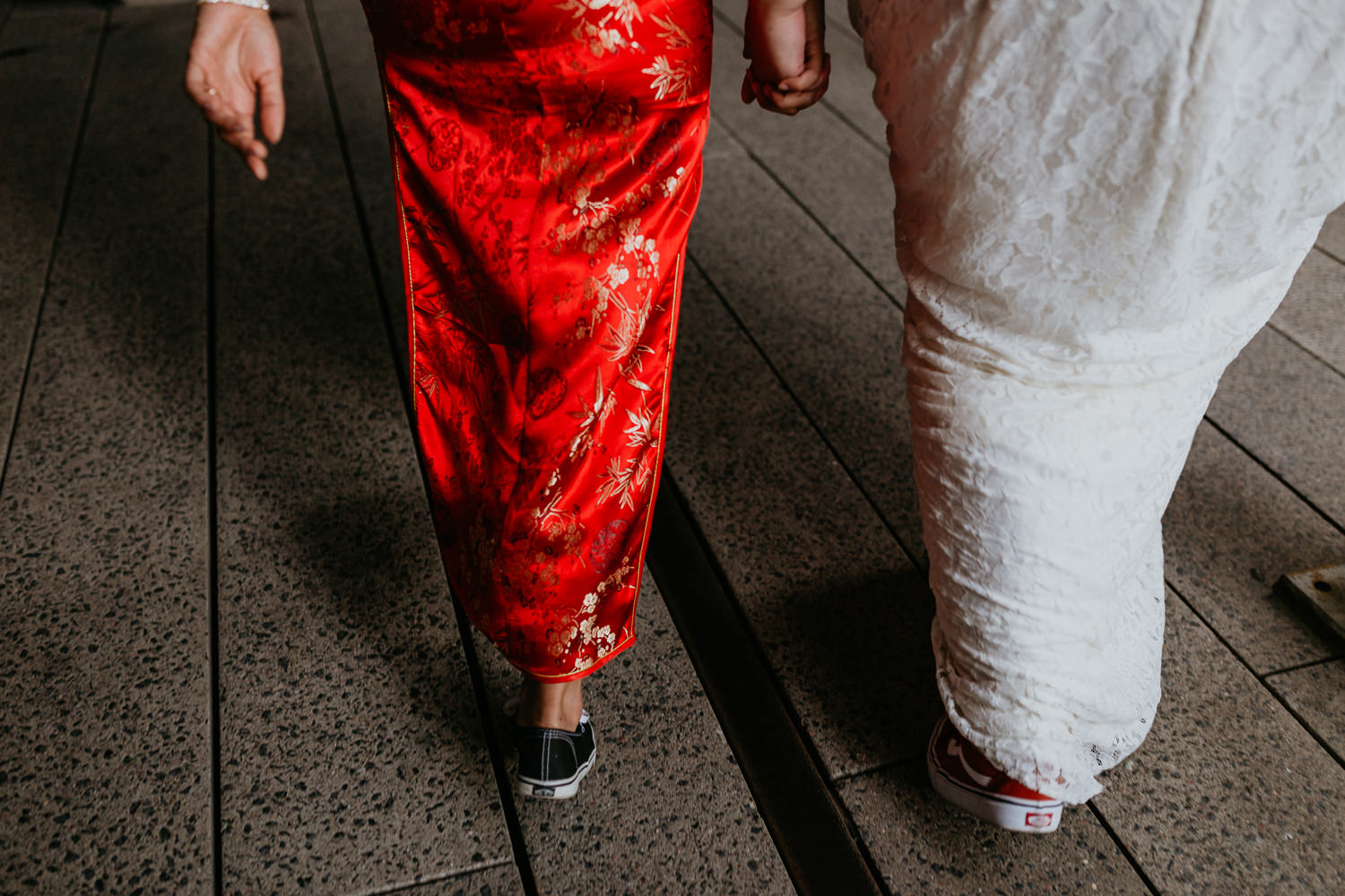 close up waist down from behind of two brides walking holding hands wearing vans sneakers