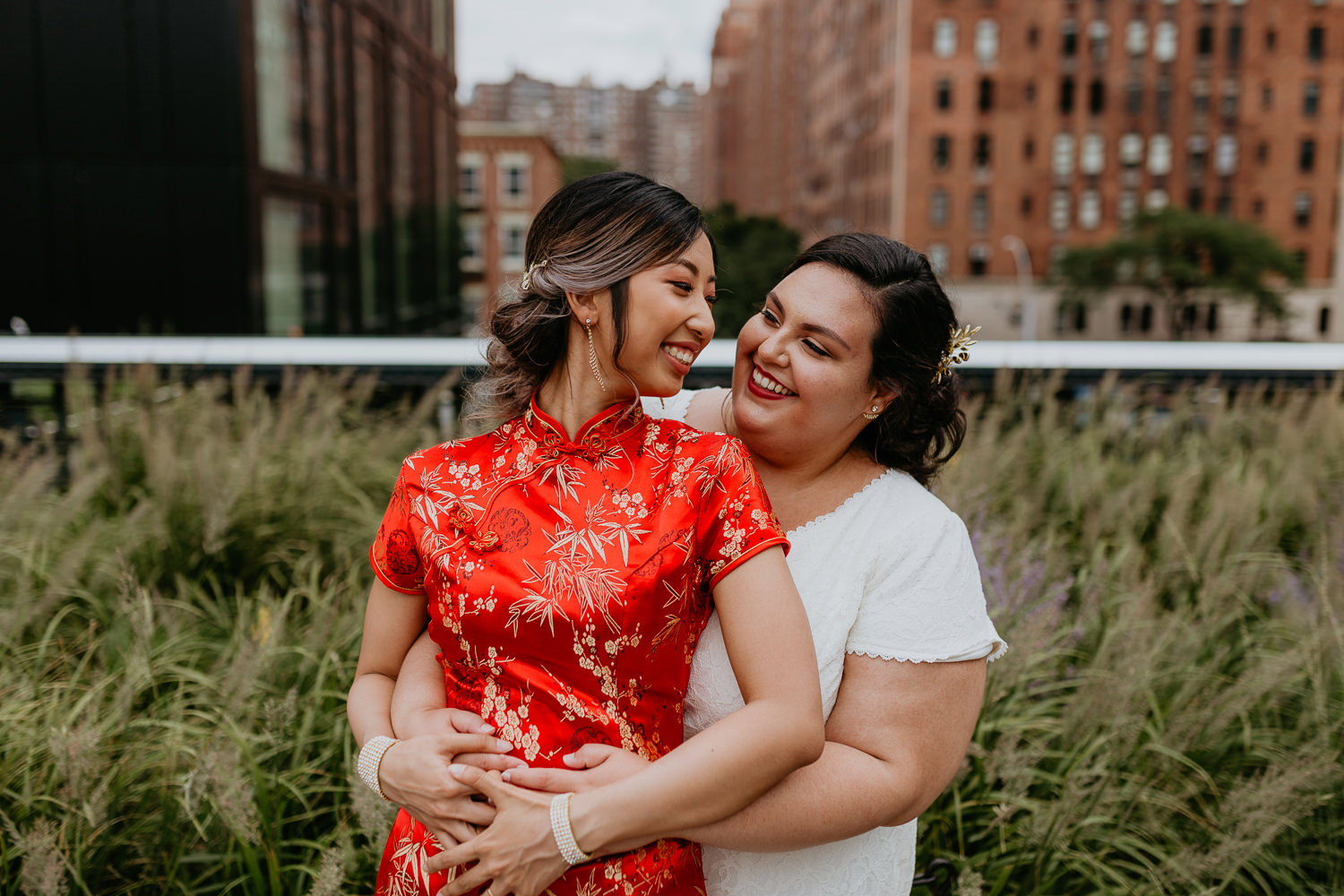 newlywed same sex brides hugging and smiling from behind with Chelsea nyc views