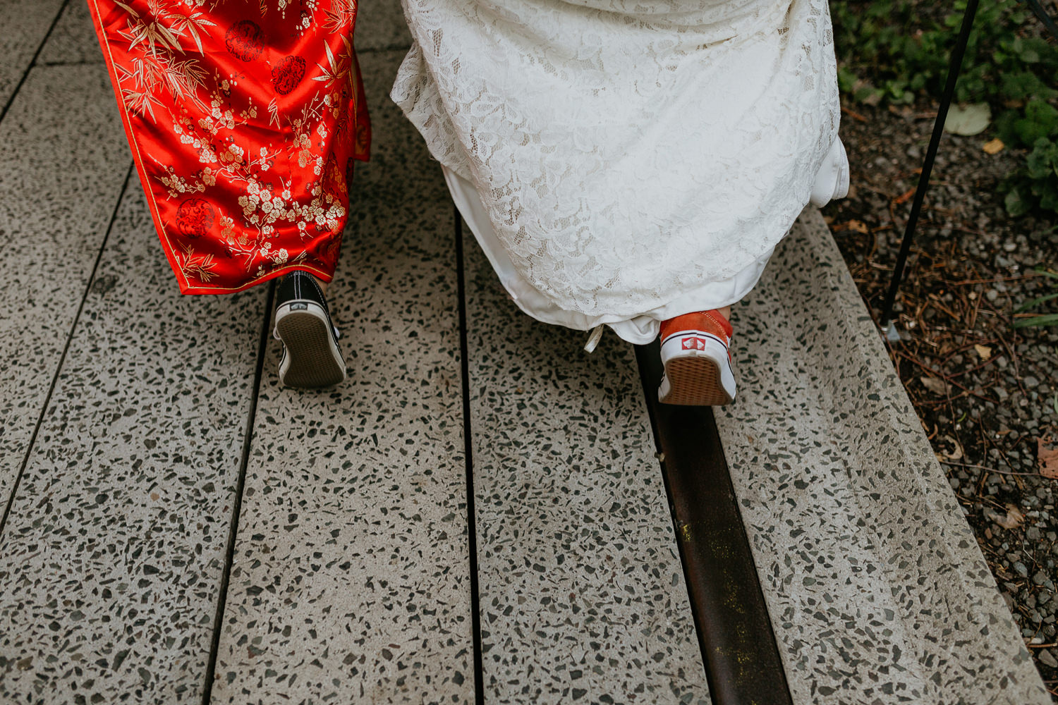 close up of brides walking from behind vans sneakers under the dresses
