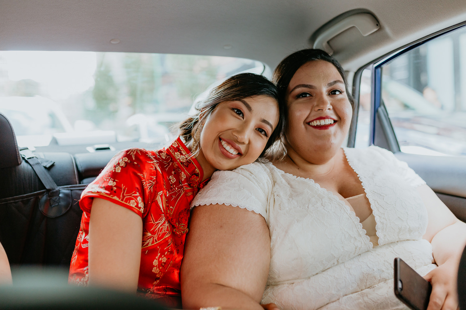 two brides in the back of the uber, one with her head on the others shoulder