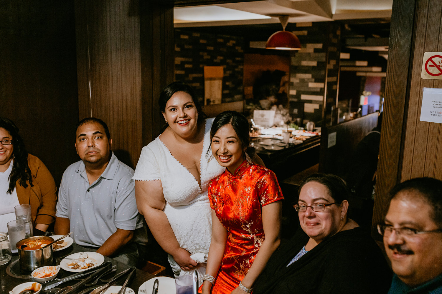 two brides posing with family at reception Chinese restaurant