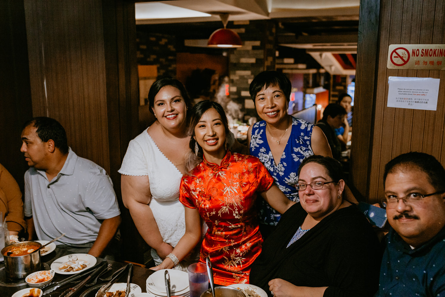 two brides posing with family at Chinese restaurant reception